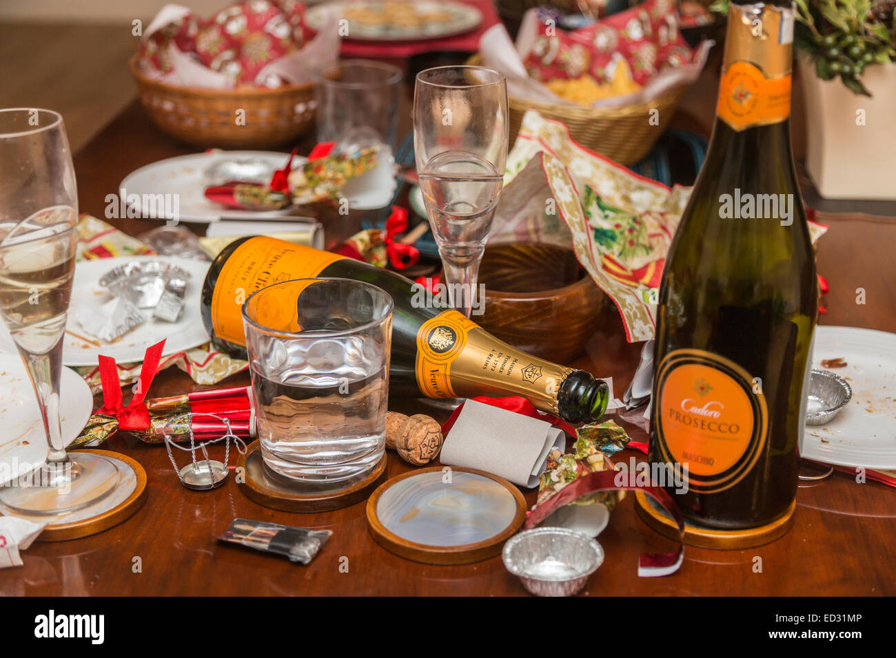 Debris, rubbish and unwashed glasses in the aftermath of a festive season party with an empty Veuve Clicquot champagne - Stock Image