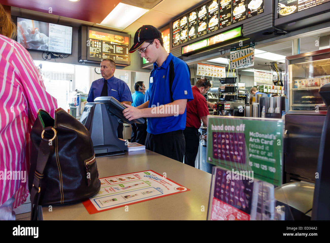 Illinois Gibson City McDonald's fast food restaurant counter man employee working job uniform order order taker - Stock Image