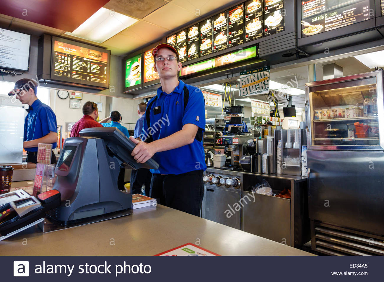Illinois Gibson City McDonald's fast food restaurant counter man employee working job uniform order taker cashier - Stock Image