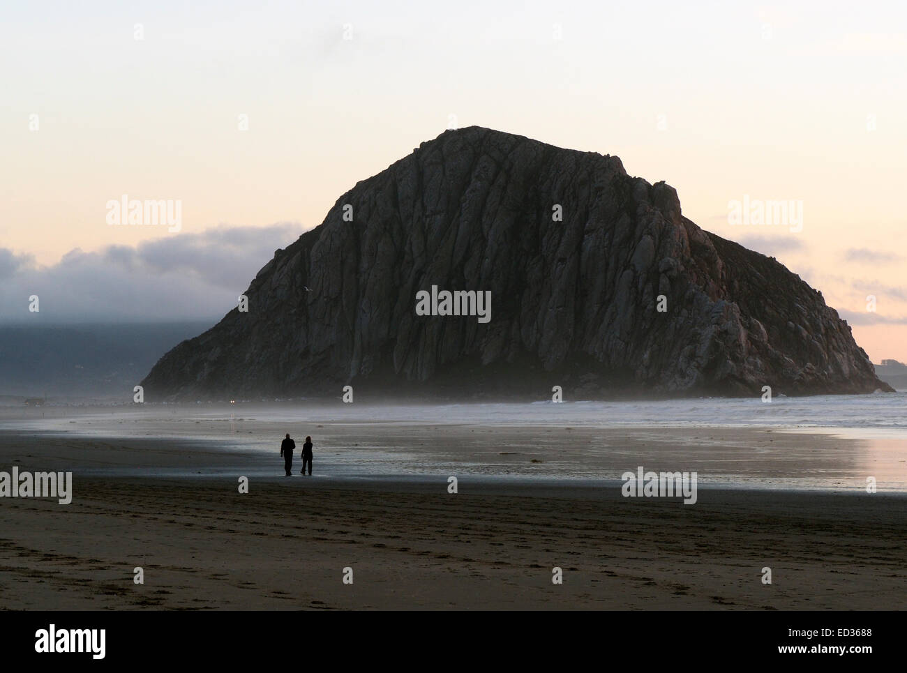 Two People Strolling on the beach near Morro Rock - Stock Image