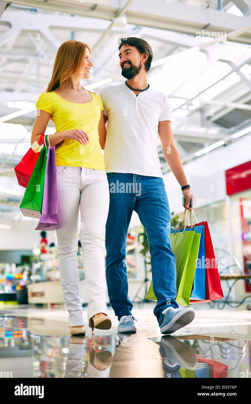 Amorous couple with paperbags buying presents in the mall - Stock Image