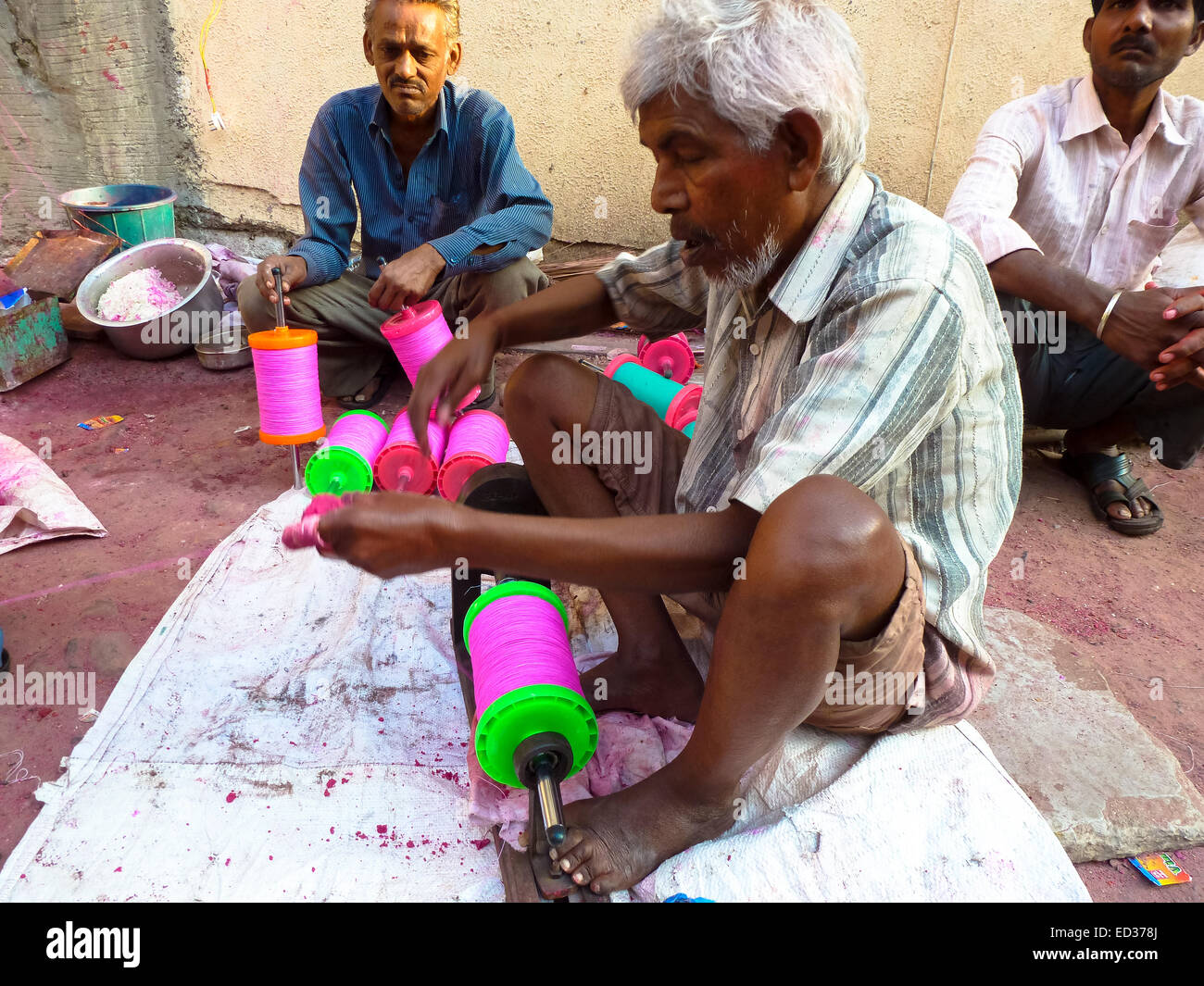 man coloring threads with colors at street in ahmedabad gujarat india - Stock Image