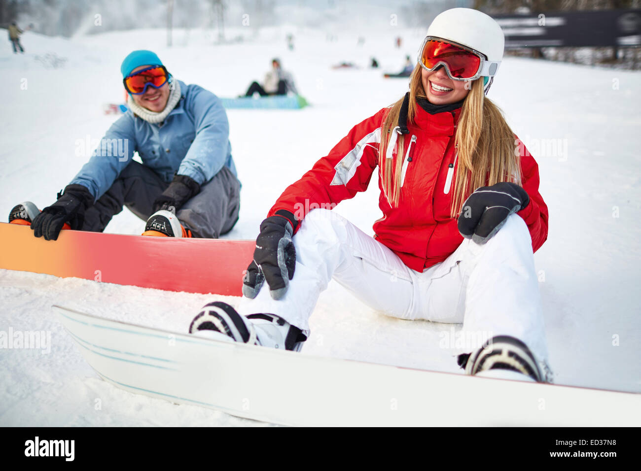 Sporty girl with snowboard spending winter vacations with her boyfriends - Stock Image