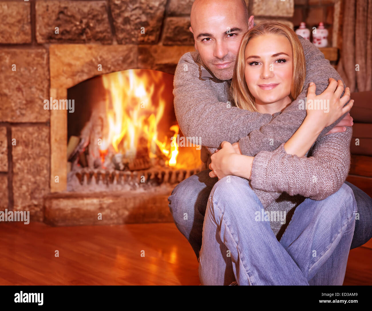 Portrait of gentle couple sitting near fireplace at home, romantic celebration of Christmas holidays, love and togetherness - Stock Image