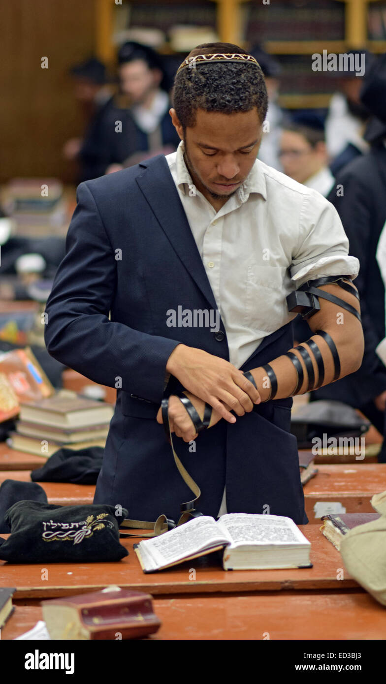 A young African American religious Jew putting on teffilin at a synagogue in Brooklyn, New York - Stock Image