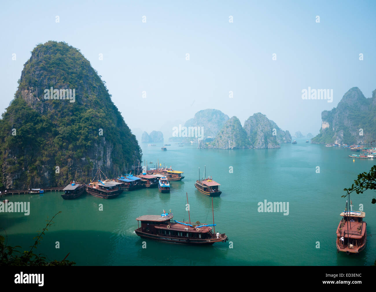 A view of the spectacular limestone karst formations rising above boats moored in Halong Bay, Vietnam. - Stock Image
