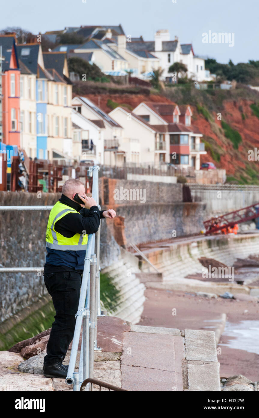 Security guard talking on mobile phone on the seawall at Dawlish - Stock Image