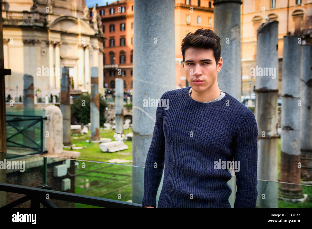 Handsome young man in Rome standing in front of Foro Traiano and Fori Imperiali, looking at camera - Stock Image