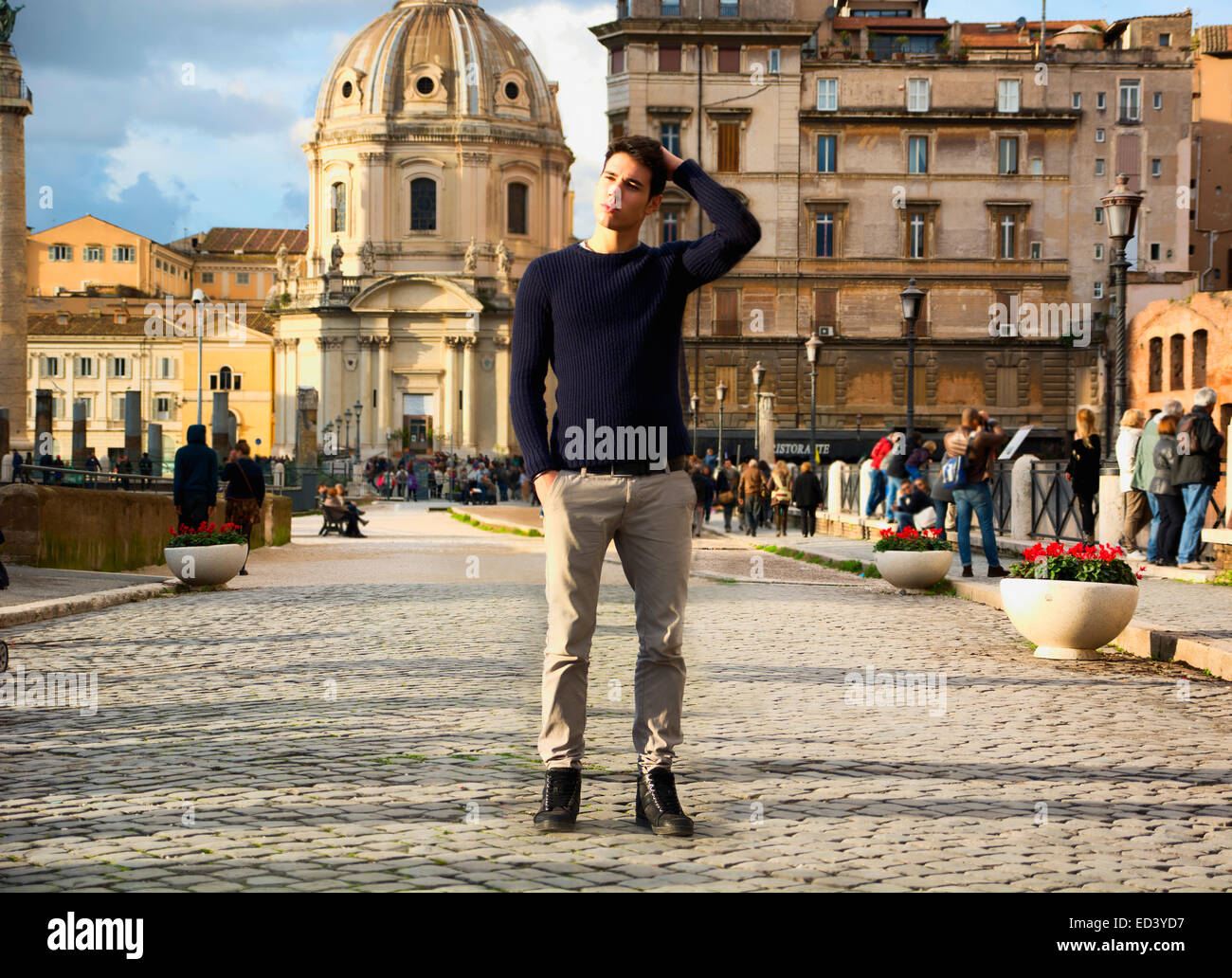Attractive young man in Rome standing in front of Santa Maria di Loreto church, looking away - Stock Image