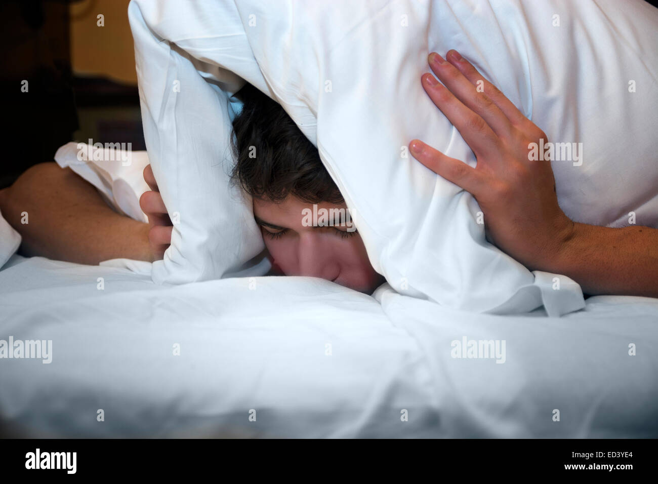 Handsome young male insomniac covering his head and ears trying to block out the sound with a pillow as he is kept - Stock Image