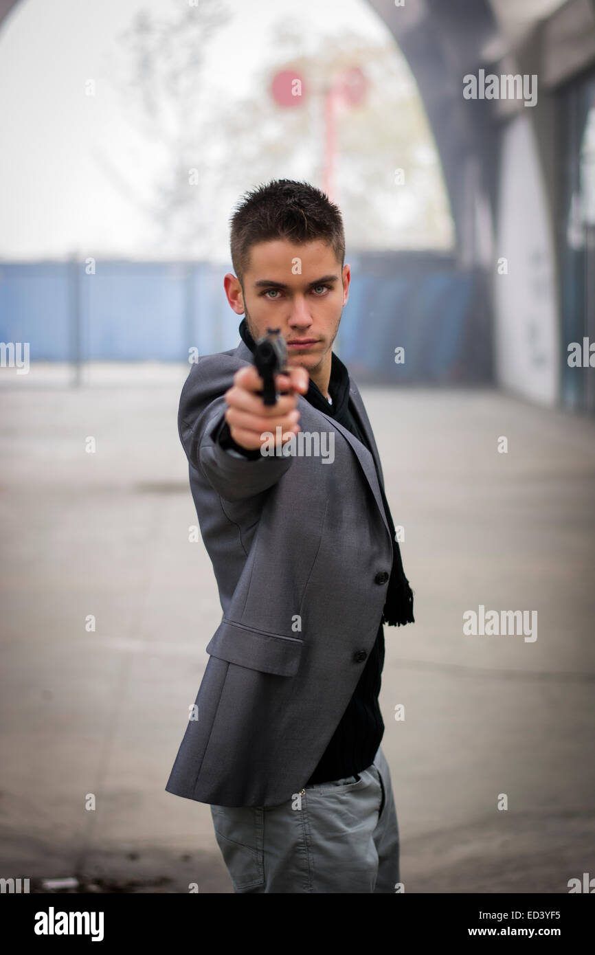 Well dressed handsome young detective or policeman or mobster standing in an urban environment aiming a firearm - Stock Image