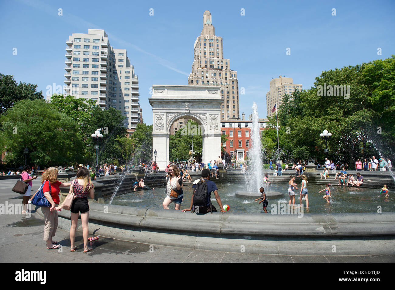 NEW YORK CITY, USA - JUNE 2014: People gather at the fountain in Washington Square Park on a bright summer afternoon. Stock Photo