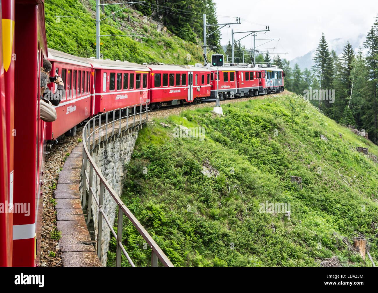 Rhatische Bahn train en route to St. Moritz in Switzerland above Poschiavo on the Bernina railway route - Stock Image