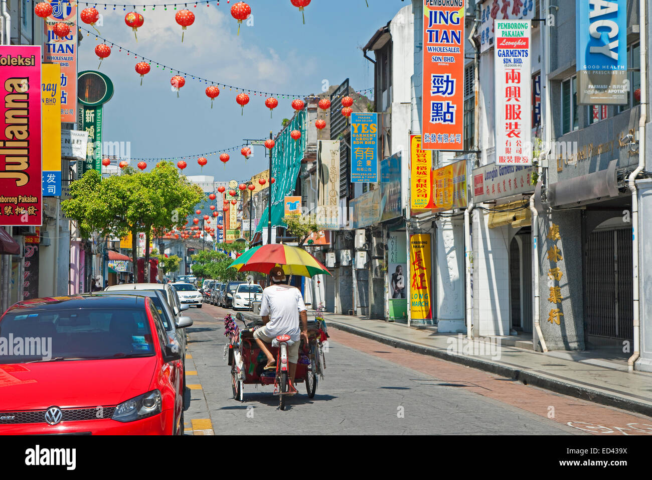Cycle rickshaw / beca with umbrella riding through shopping street in the city George Town / Georgetown, Penang, - Stock Image