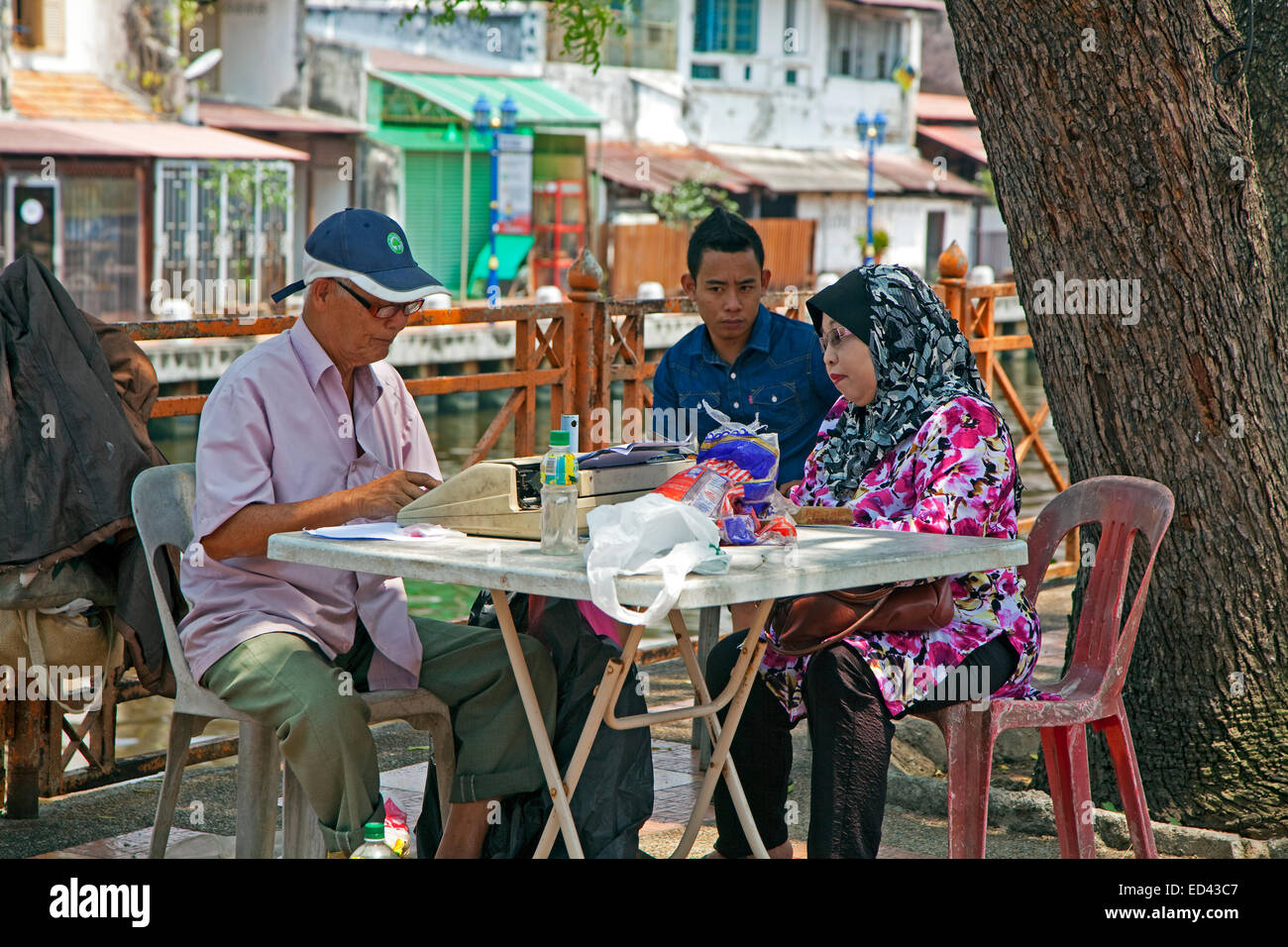 Elderly Malaysian man typing letter on portable typewriter in the streets of Malacca, Malaysia Stock Photo