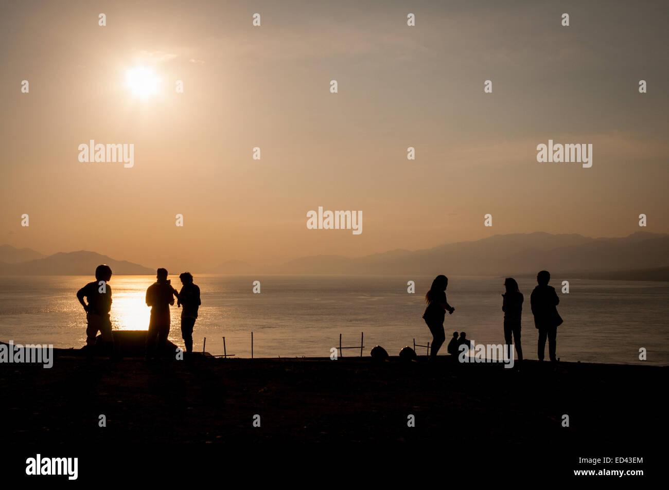 Local people silhouetted against a bright sky at Waijarang beach, Lembata Island, Indonesia. © Reynold Sumayku - Stock Image
