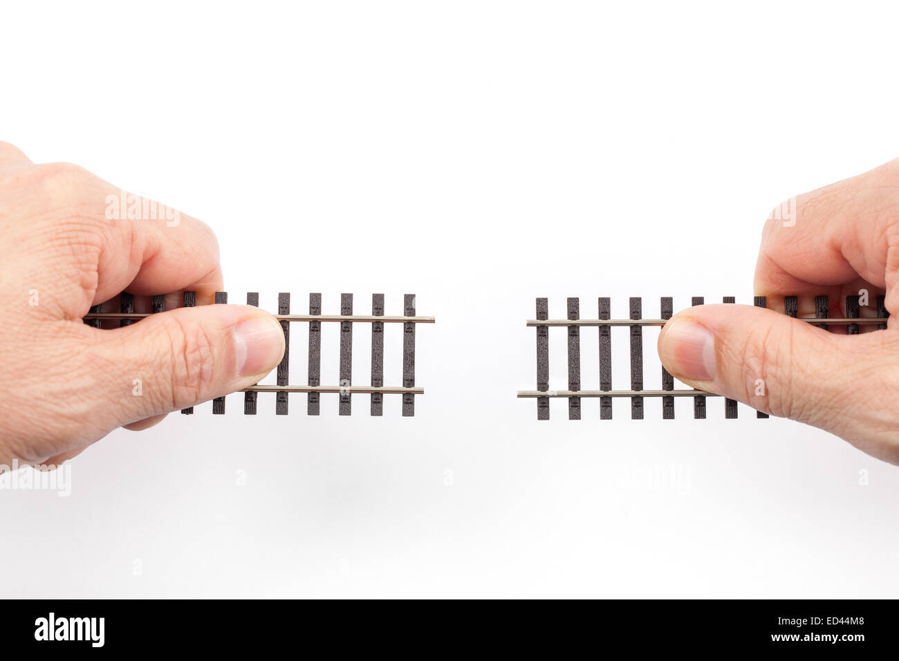 Railroad tracks toys in two hands ready for connecting isolated on white background - Stock Image