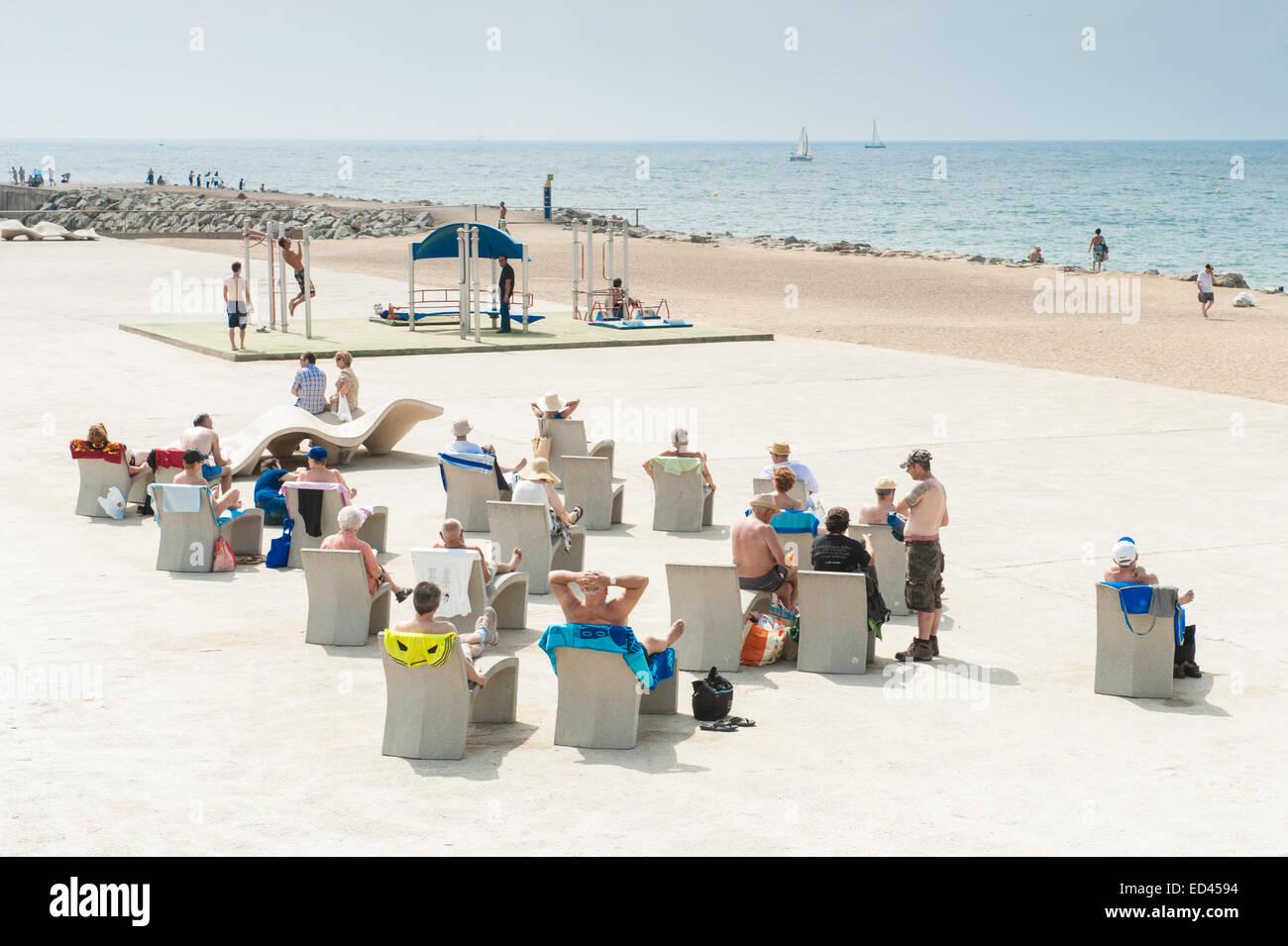 Barcelona city beach sunbathers sitting on cement sun loungers, Barcelona, Catalonia, Spain - Stock Image