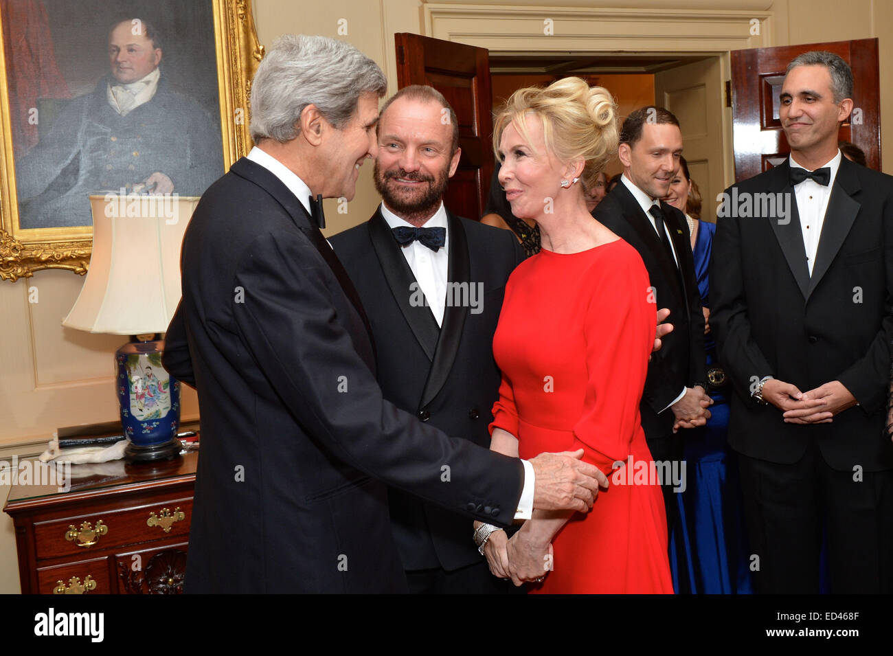 U.S. Secretary of State John Kerry greets 2014 Kennedy Center Honoree singer-songwriter Sting and his wife, Trudie Styler, before a dinner he hosted in honor of the Honorees at the U.S. Department of State in Washington, D.C., on December 6, 2014. Stock Photo
