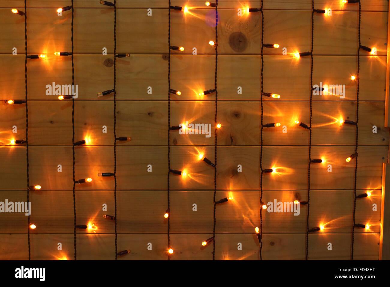 Christmastime ornament, little decorative adorned x-mas lights, wood glowing background - Stock Image