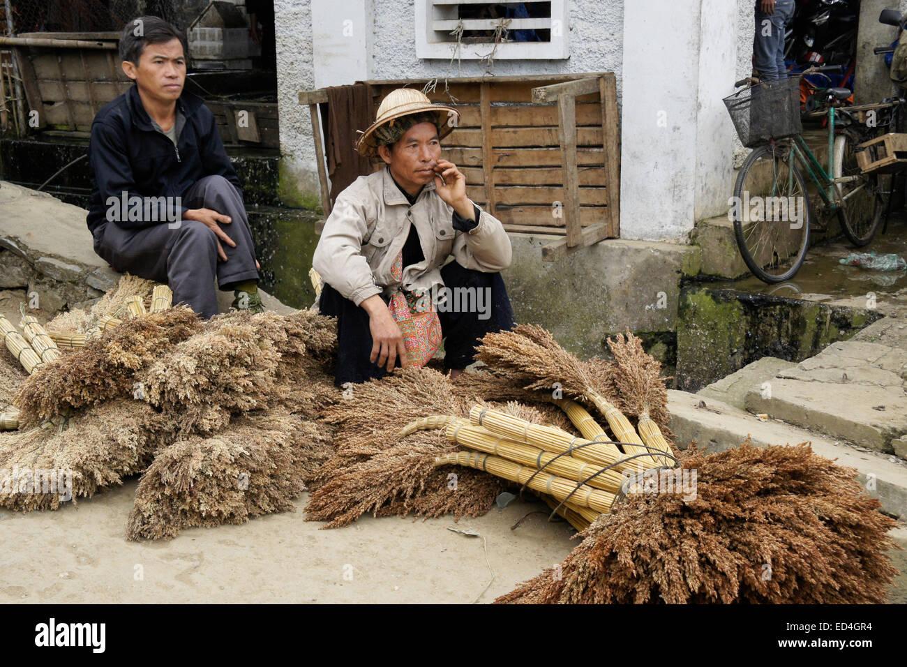 Men selling brooms at Sunday Market, Bac Ha, Sapa (Sa Pa), Vietnam - Stock Image
