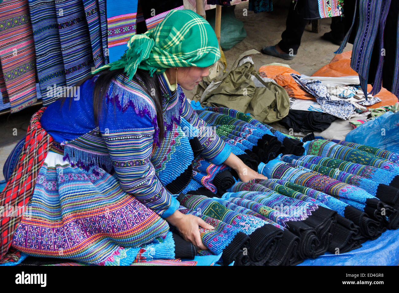 Flower Hmong woman selling pleated skirts at Sunday Market, Bac Ha, Sapa (Sa Pa), Vietnam - Stock Image
