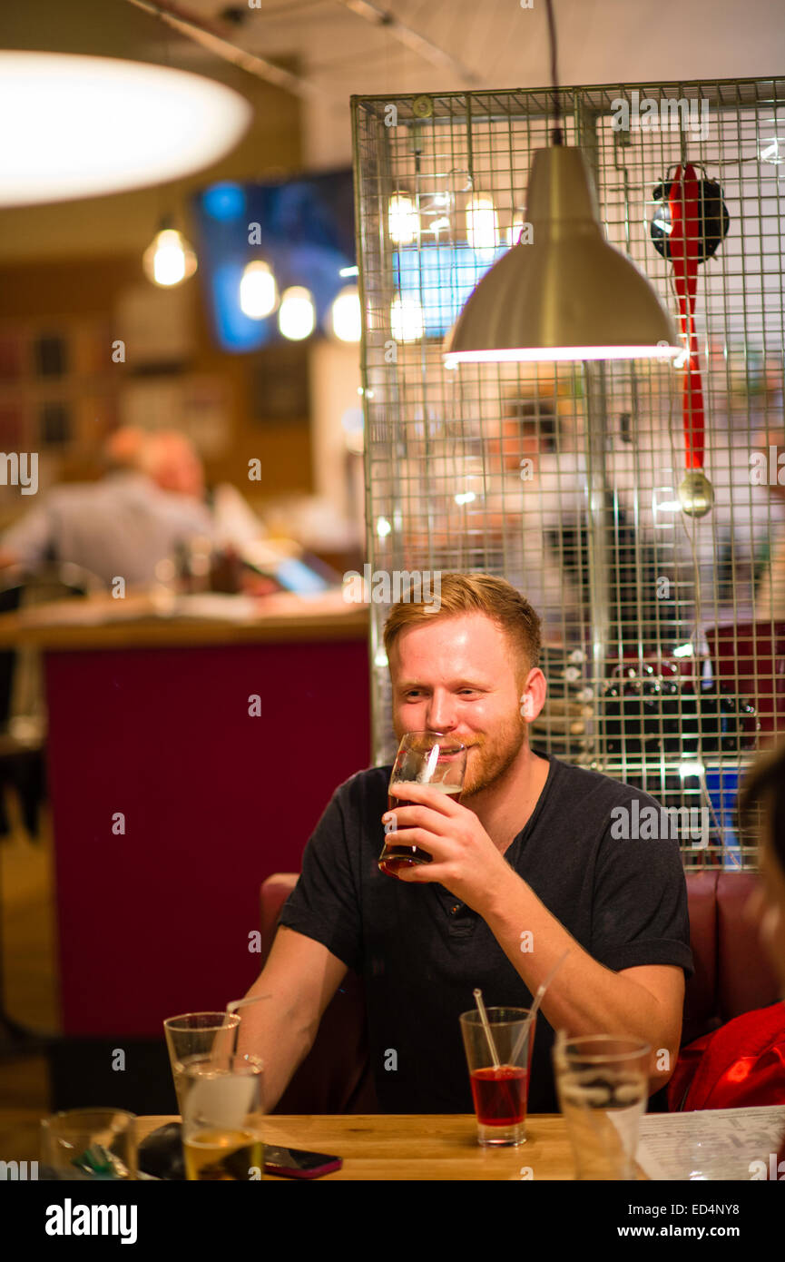 A bearded hipster young man drinking a pint of beer in a modern  bar club pub uk - Stock Image