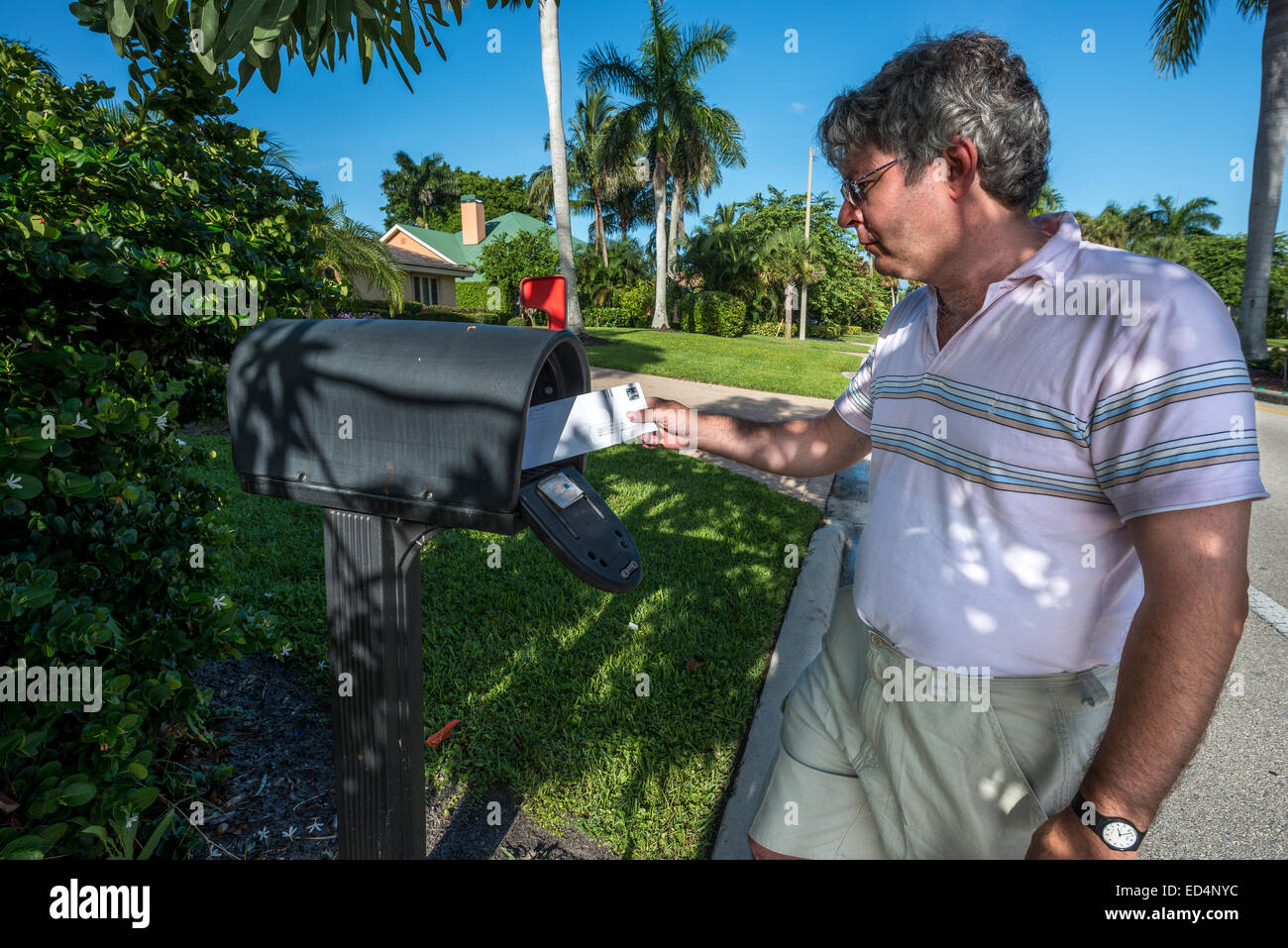 man at mailbox; naples; florida; usa; letters; roadside; residential street - Stock Image