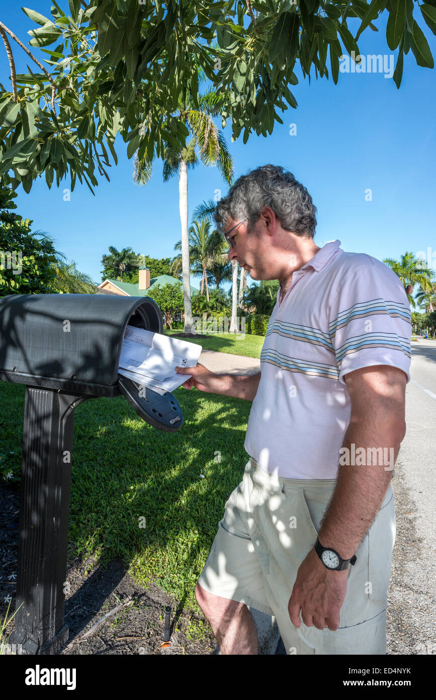 man at postbox; naples; florida; usa; letters; roadside; residential street - Stock Image