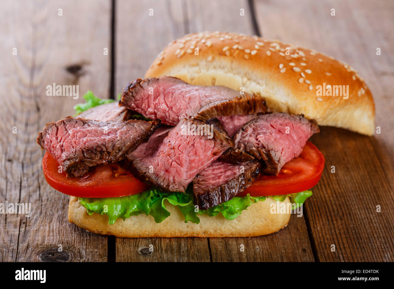 roast beef hamburger sandwich on a wooden surface - Stock Image