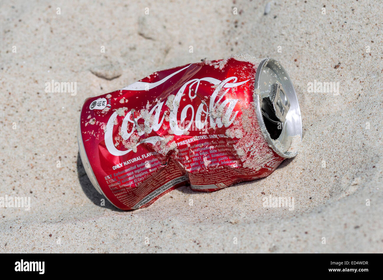 Photo of empty and crashed Coca-Cola can lying on the beach sand - Stock Image