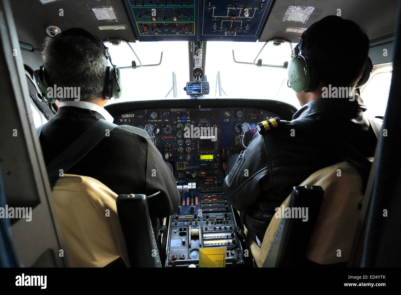 pilots in a propeller airplane flying to Lukla Tenzing Hillary airport with the dramatic Himalaya mountains, Himalayas, - Stock Image