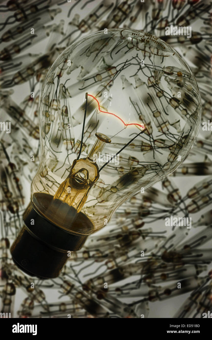 Glowing supported red hot tungsten wire filament in clear light bulb chamber indicating flow of electricity and - Stock Image