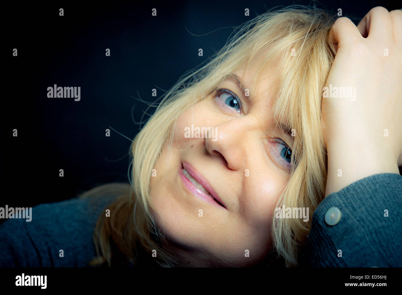 portrait blond woman in her forties, happy and satisfied - Stock Image
