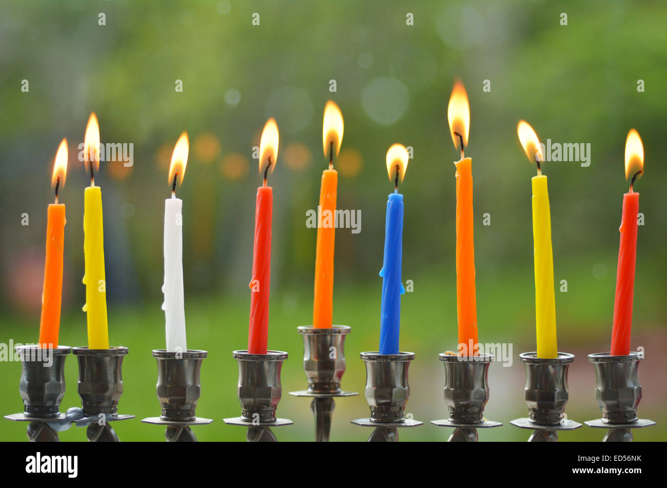 Hanukkah menorah lit with eight candles at the last day of Hanukah. - Stock Image
