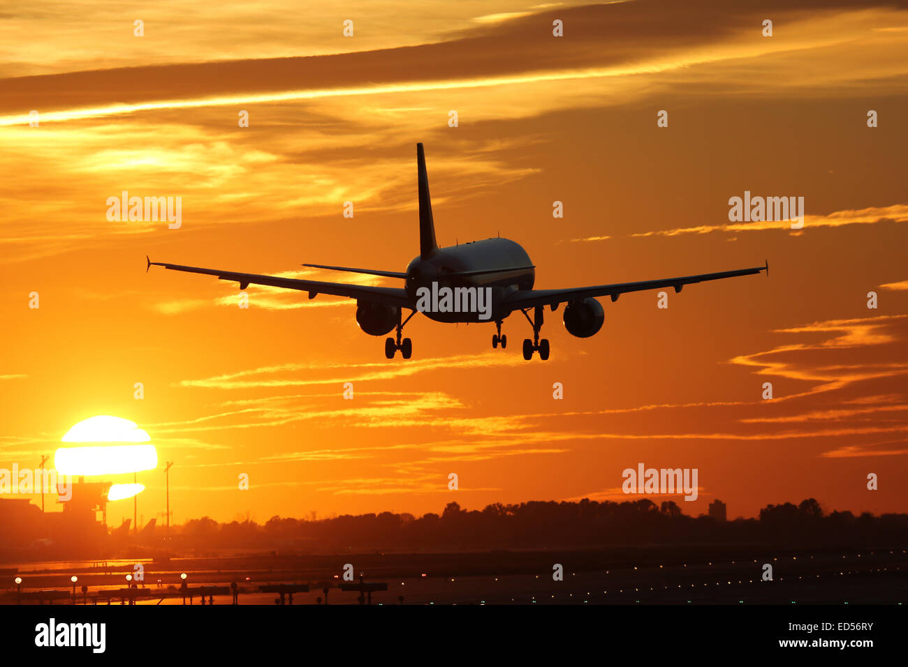 An airplane landing at an airport during sunset on vacation during a journey - Stock Image