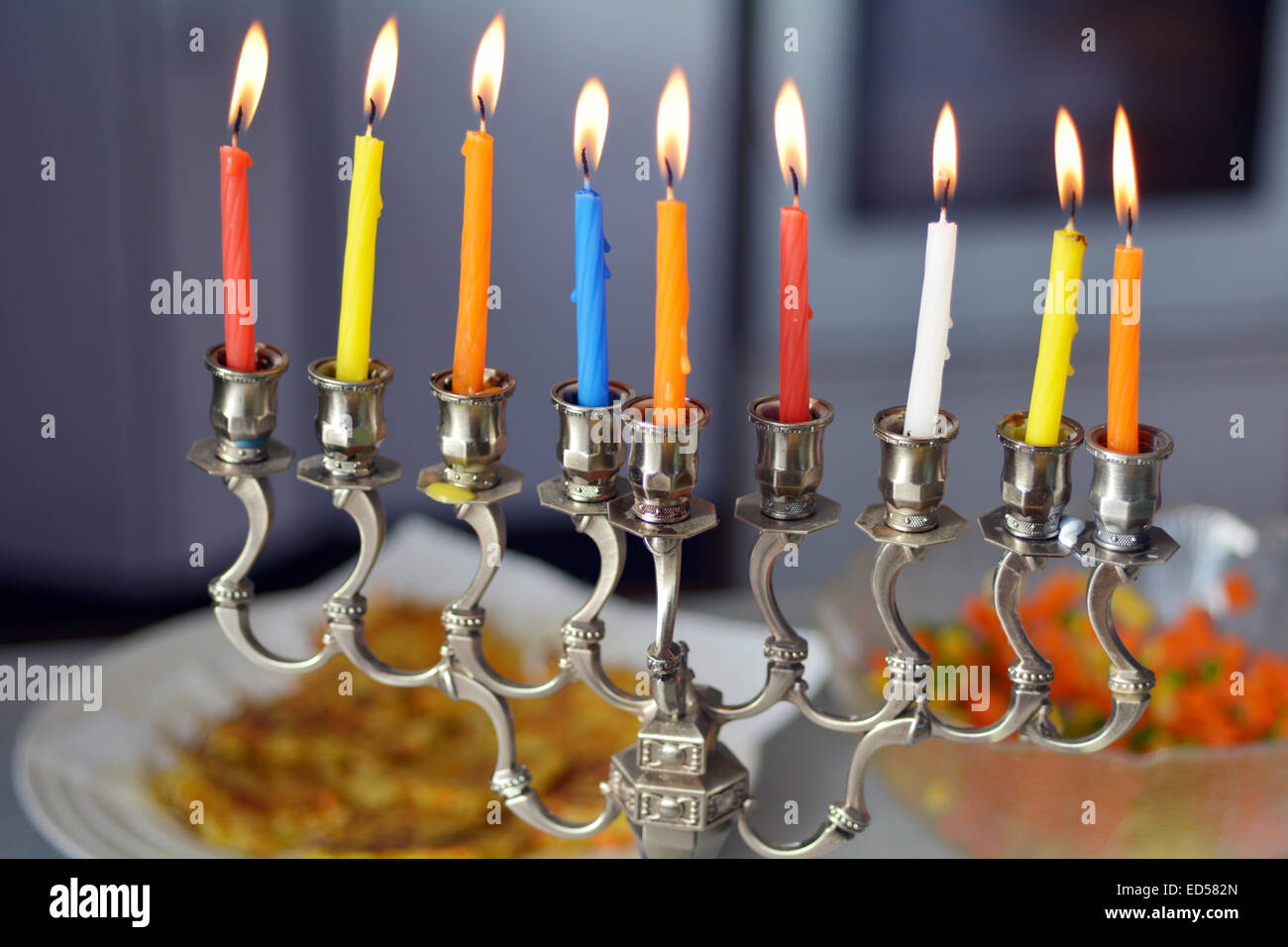 Hanukkah menorah lit with eight candles during dinner celebration at the last day of Hanukah. - Stock Image