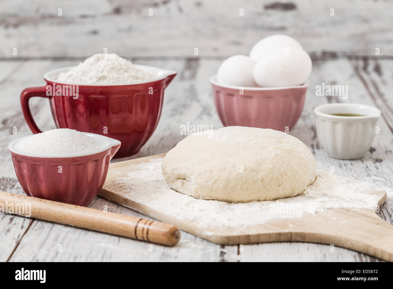 Dough recipe ingredients like eggs, flour, oil, sugar on white wooden table - Stock Image
