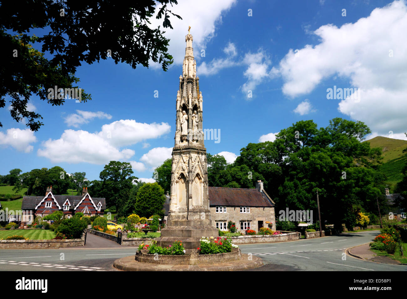 A tall Gothic monument on a roundabout with stone clad cottages behind. - Stock Image