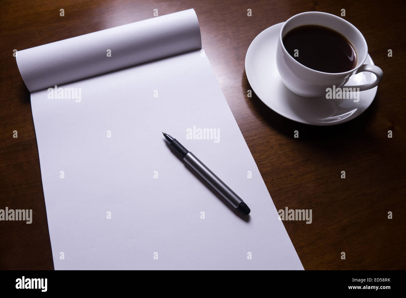 sheet of paper, pen and cup of coffee on desk - Stock Image