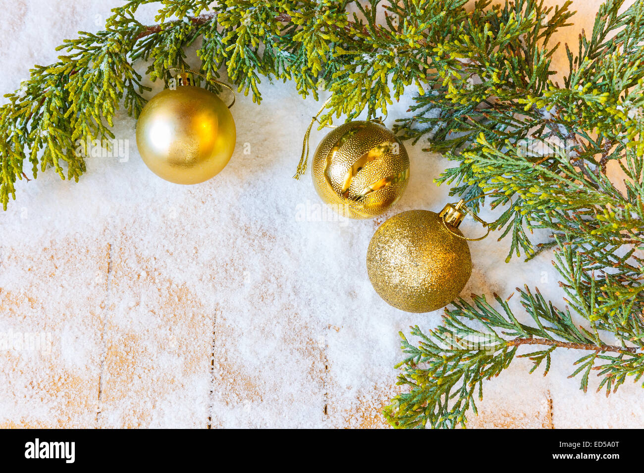 Christmas decorations and Christmas tree branch in the snow - Stock Image