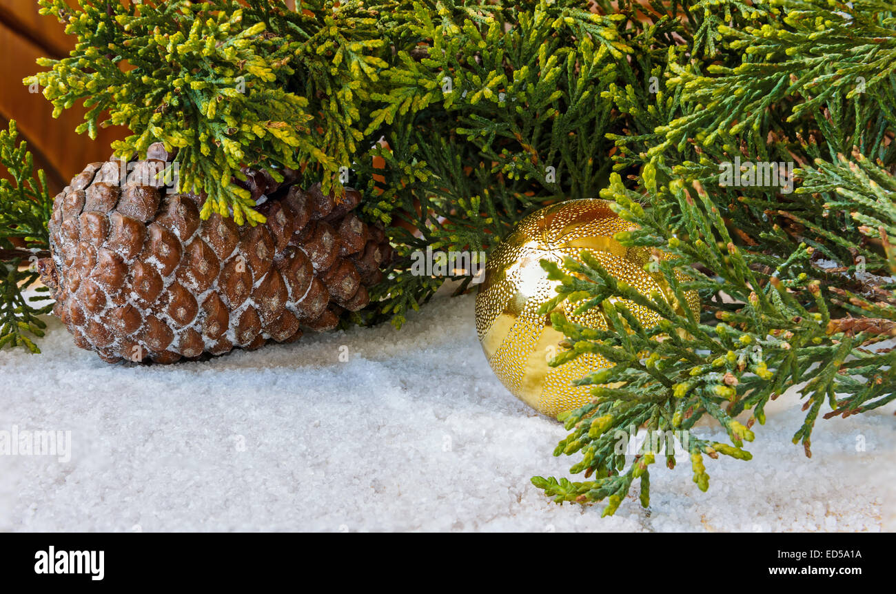 Christmas decorations, pine cones and Christmas tree branch in the snow - Stock Image