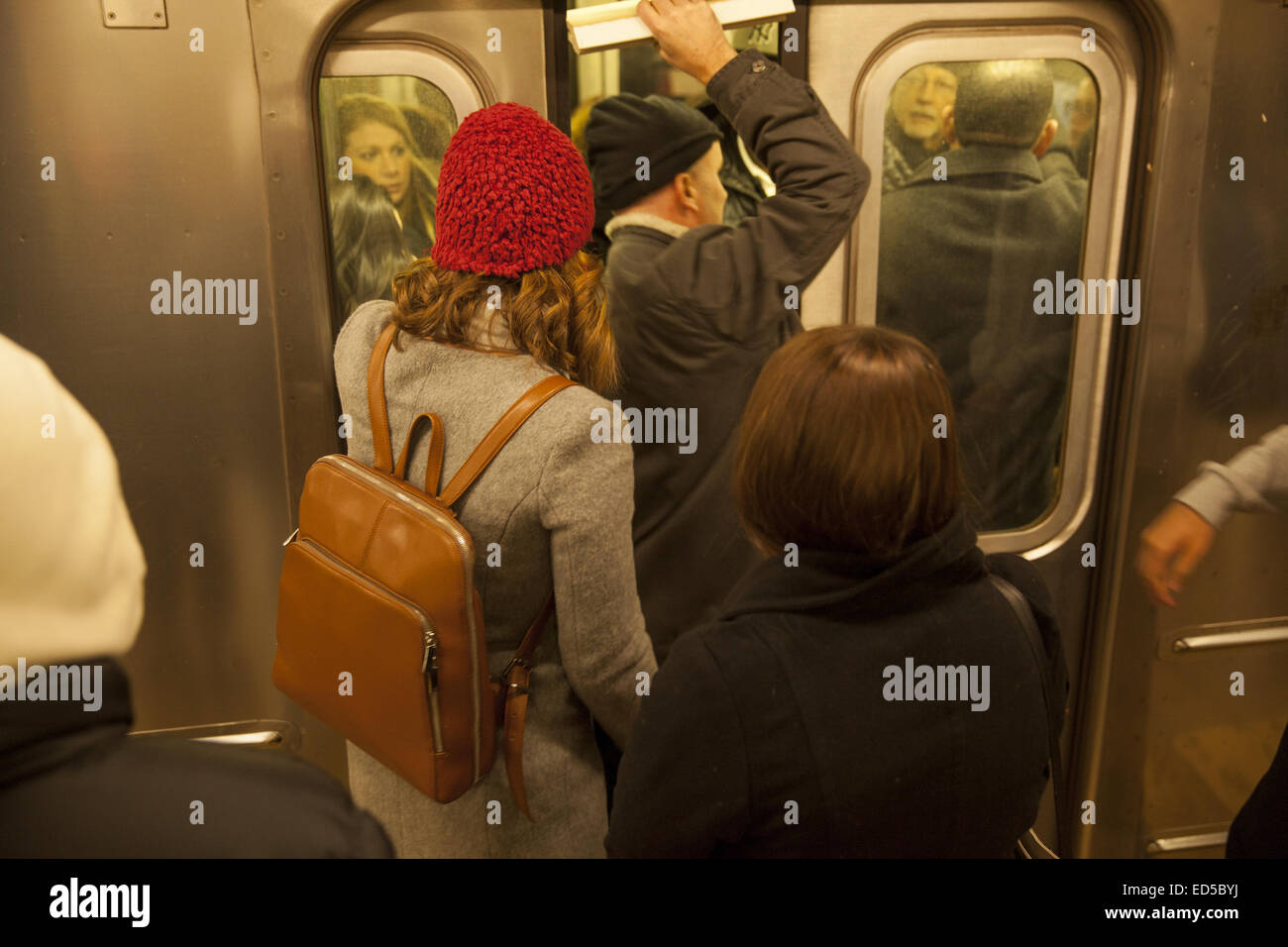 Man tries to squeeze into a subway car when the doors were closing at the Grand Central subway station in NYC. during - Stock Image