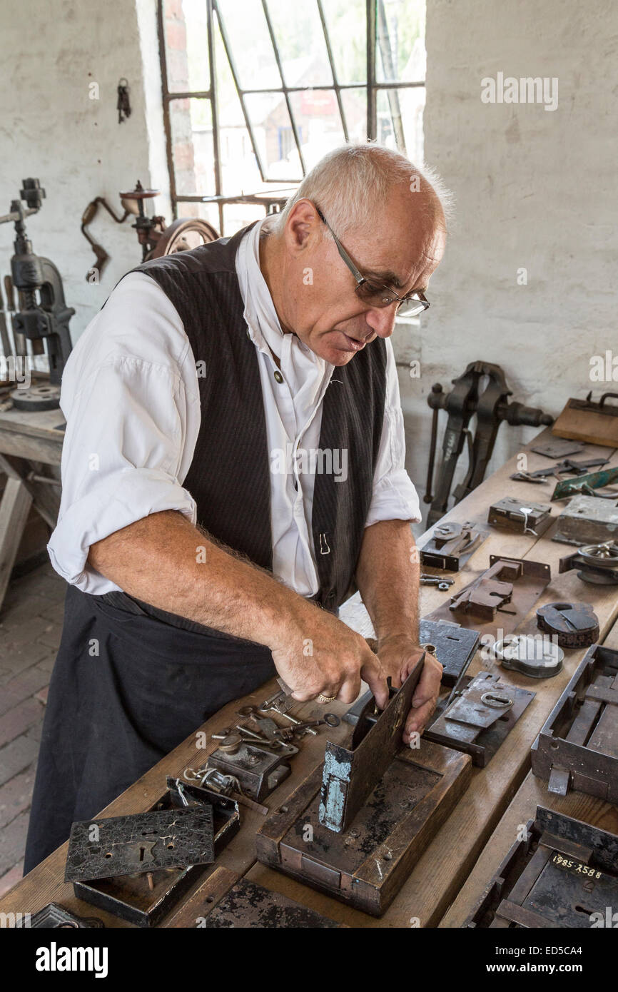 Locksmith demonstrating lock mechanism, Blists Hill Victorian town, Ironbridge, Shropshire, England, UK - Stock Image