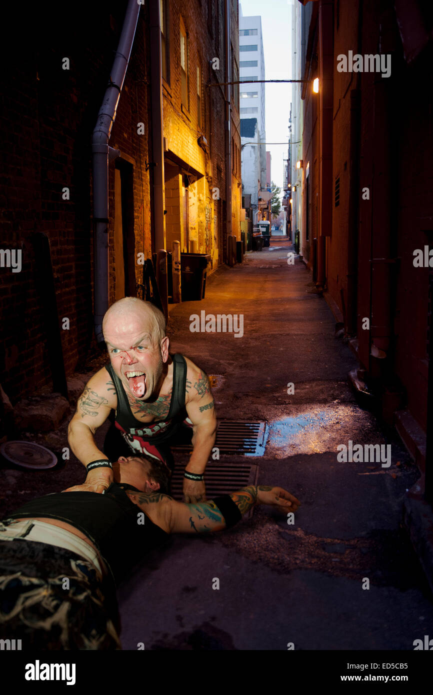 The wrestlers from 'The Half Pint Brawlers',  'Puppet' and Eric Smallz, battle it out in an alleyway - Stock Image