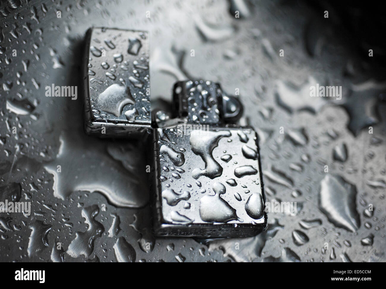 Zippo Lighter in the Rain, Still Life with lighter and water droplets - Stock Image