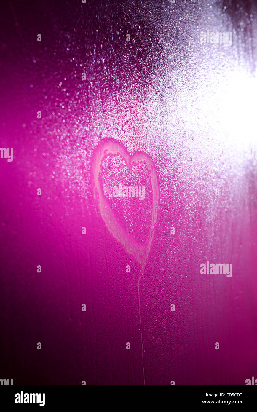 Heart drawn on steamy shower door with a pink / purple light shining behind it - Stock Image