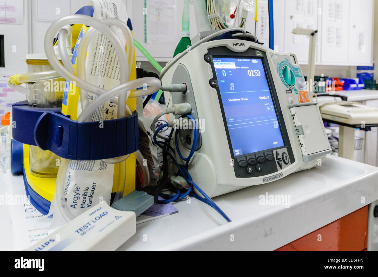 Defibrillator sitting ready for use on a hospital Crash Trolley. - Stock Image