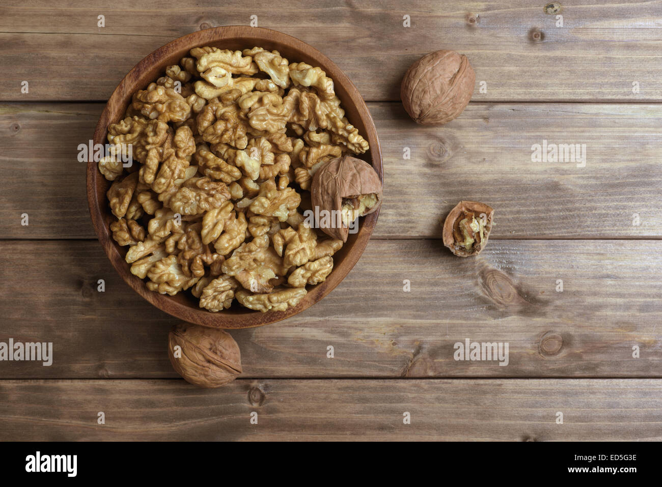 Walnuts in wooden bowl on wooden table - Stock Image