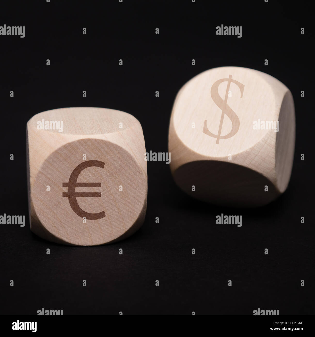 dice with dollar and euro symbol on black background - Stock Image